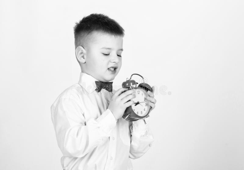 Kid adorable boy white shirt red bow tie. Develop self discipline. Set up alarm clock. Child little boy hold red clock. It is time. Schedule and timing stock photos