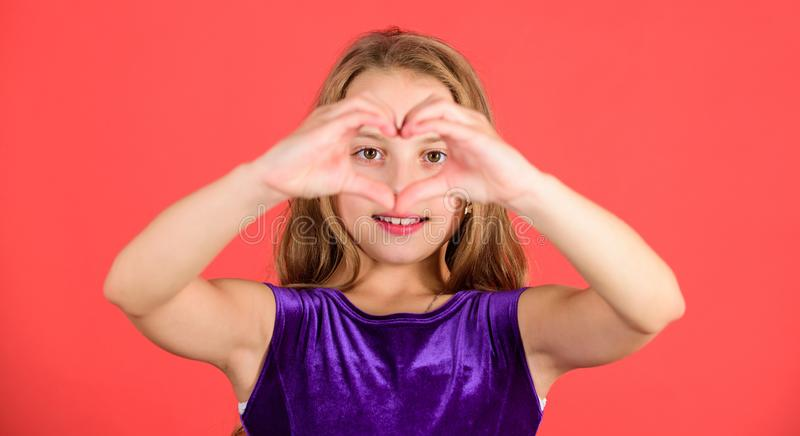Kid adorable girl with long hair smiling face show heart gesture to you. Celebrate valentines day. Love and sympathy. Love concept. Girl cute child show heart stock image