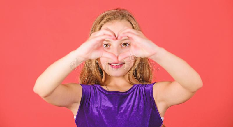 Kid adorable girl with long hair smiling face show heart gesture to you. Celebrate valentines day. Love and sympathy. Love concept. Girl cute child show heart stock photo