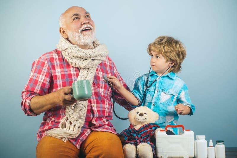 Kid aide l'homme âgé à prendre ses pilules Homme en foulard tricoté coloré avec médecine Petit médecin prêt à examiner photographie stock libre de droits
