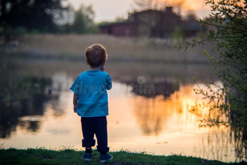 Kid alone near water. Risky moment stock images
