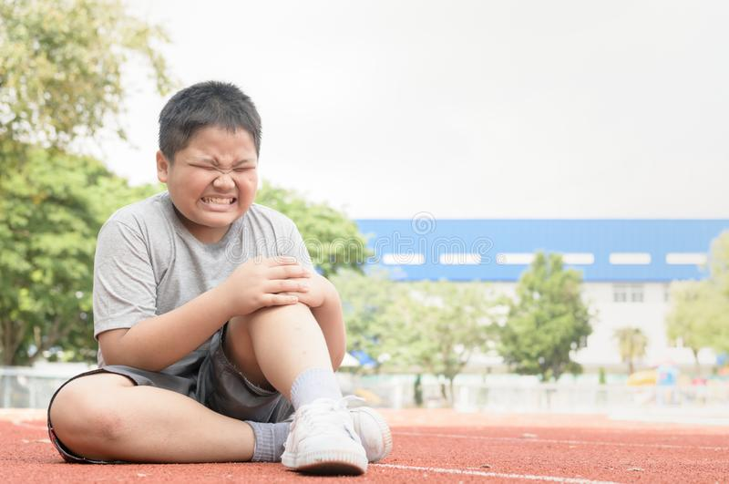 Kid athlete suffering form running knee or kneecap injury. During outdoor workout on track royalty free stock photo