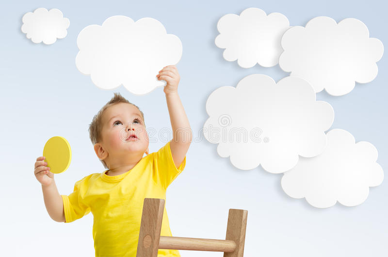 Kid attaching cloud to sky using ladder concept stock photos