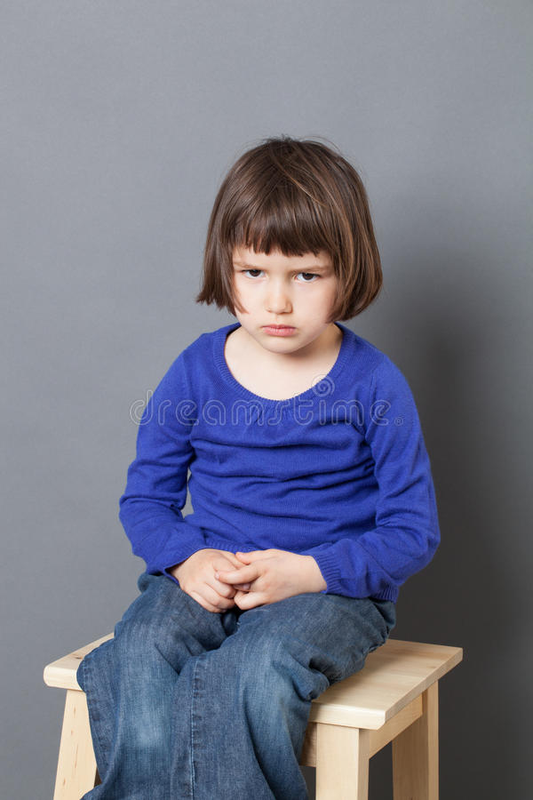 Kid attitude concept for sulking 4-year old child. Kid attitude concept - unhappy 4-year old child sulking on a stool for discipline or calming down in the royalty free stock photography