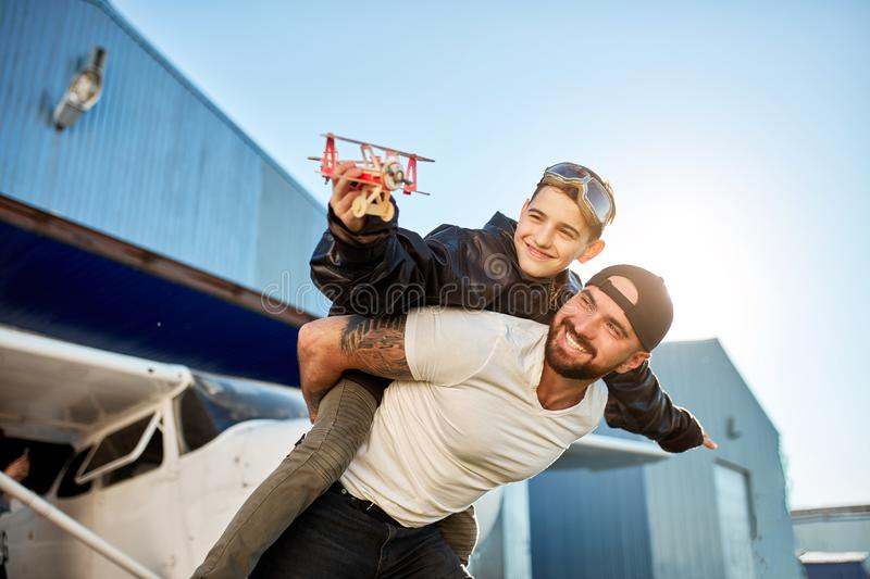 Kid in aviator glasses with model airplane, sitting on his big brother`s back royalty free stock photos