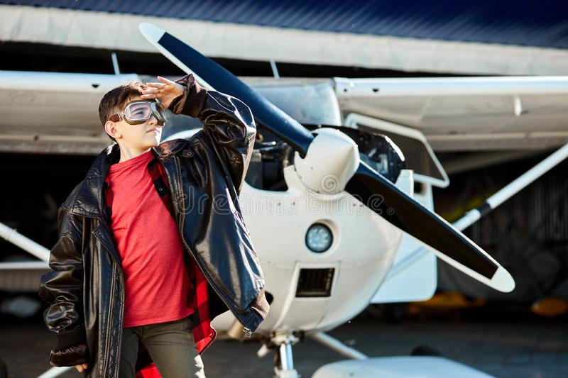 Kid in aviator glasses stands in front of white single-engine private plane royalty free stock image