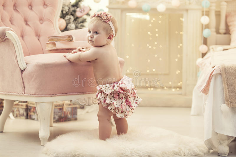Kid baby girl in pink clothes and happy interior royalty free stock photos