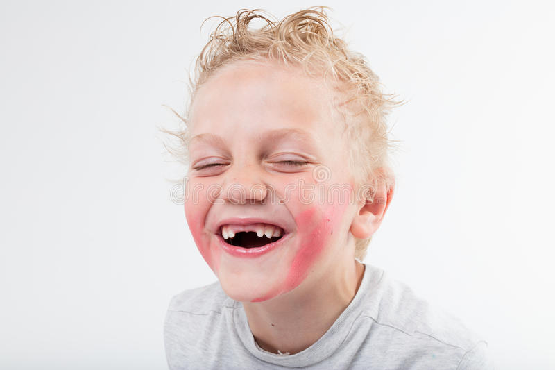 Kid baring his windowed teeth laughing. Kid is baring his teeth but he lacks of a pair exactly in the middle and he's laughing out loud stock images