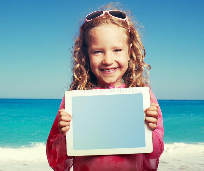 Kid on the beach with tablet pc royalty free stock photography