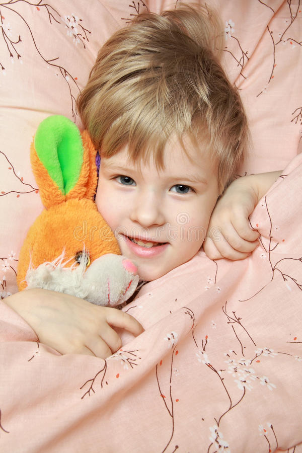 Download Kid in bed with toy stock image. Image of thoughts, blankets - 18423485