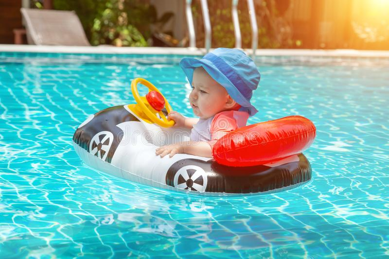 Kid behind the wheel in the pool. Summer vacation at sea. A little girl less than one year old is driving an inflatable boat in. The shape of a car royalty free stock image