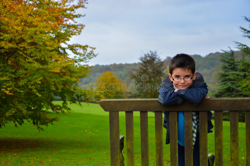 Kid on bench. A picture of a young boy sitting on a bench with arms folded looking over the back of the bench stock image