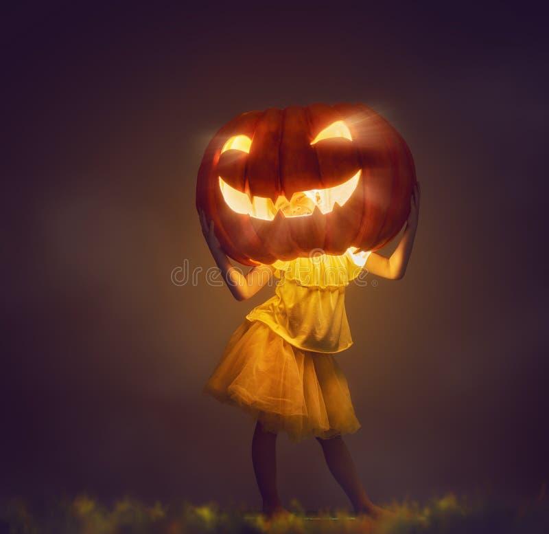 Kid with a big pumpkin head. Happy Halloween! Cute little kid with a big pumpkin head royalty free stock photography