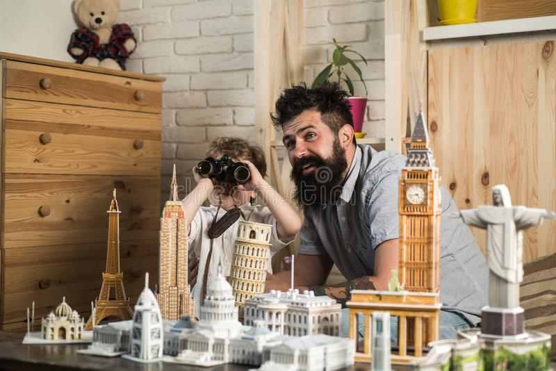 Kid with binoculars and his excited dad playing with paper models of world heritage sites, traveling around globe stock photos