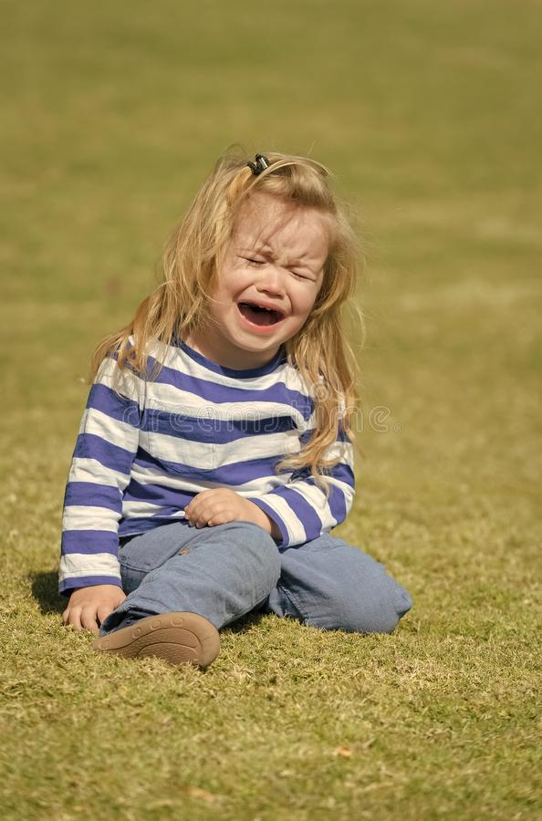 Kid with blond hair cry on idyllic sunny day. Child sit on green grass lawn. Baby boy in striped shirt and blue jeans outdoor. Childhood activity, leisure royalty free stock images