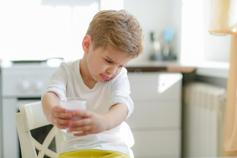 Kid or blonde happy boy eating at table. Childhood and happiness, independence. Breakfast, morning, family. Small boy stock image