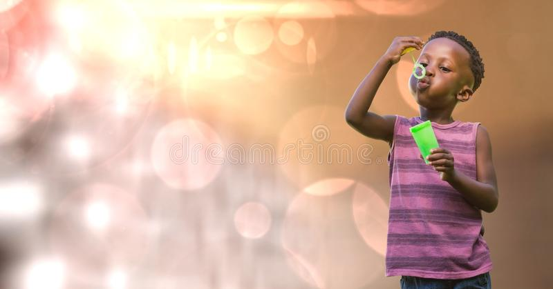 Kid blowing bubbles over blur background stock image