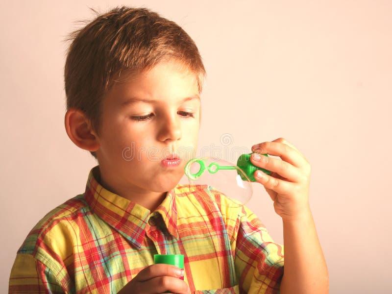 Kid Blowing Soap Bubbles stock photo