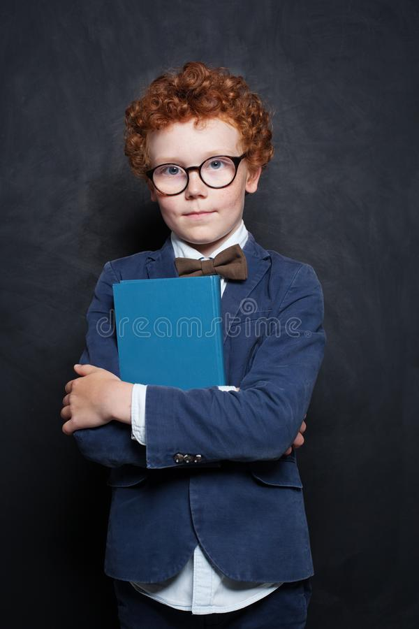 Kid and book on blackboard background. Cute child boy wearing glasses.  stock photos