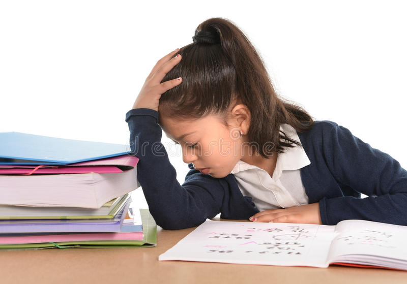 Kid bored under stress with a tired face expression in hate homework concept. Sweet little female latin child studying on desk looking bored and under stress stock photo