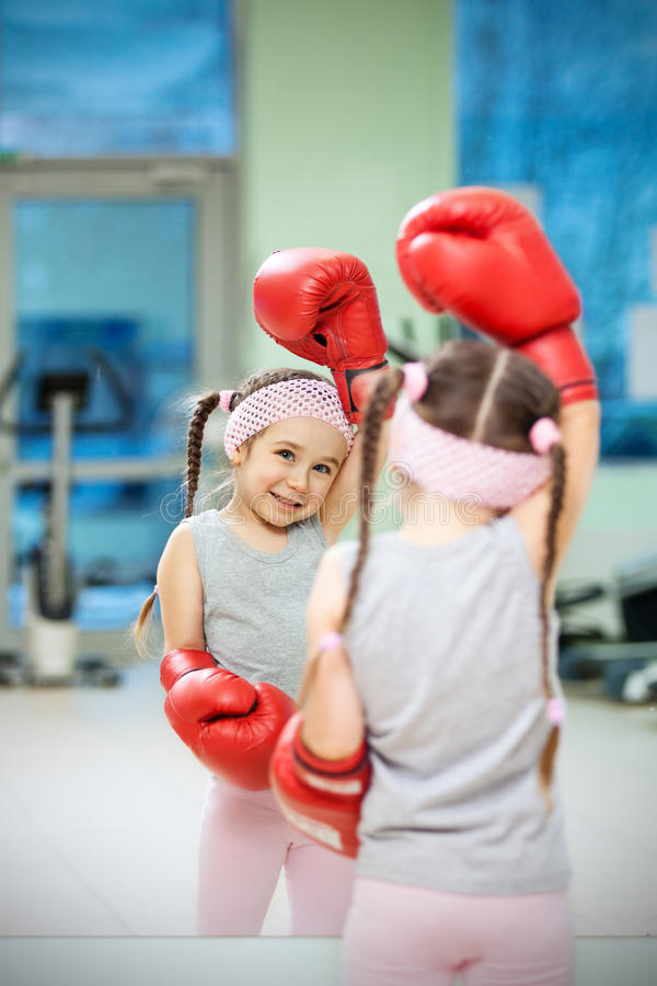Kid in boxing gloves. Near mirror stock photography