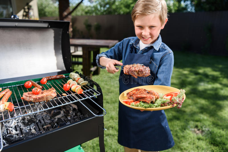 Kid boy in apron preparing tasty stakes on barbecue grill outdoors. Smiling kid boy in apron preparing tasty stakes on barbecue grill outdoors stock photography