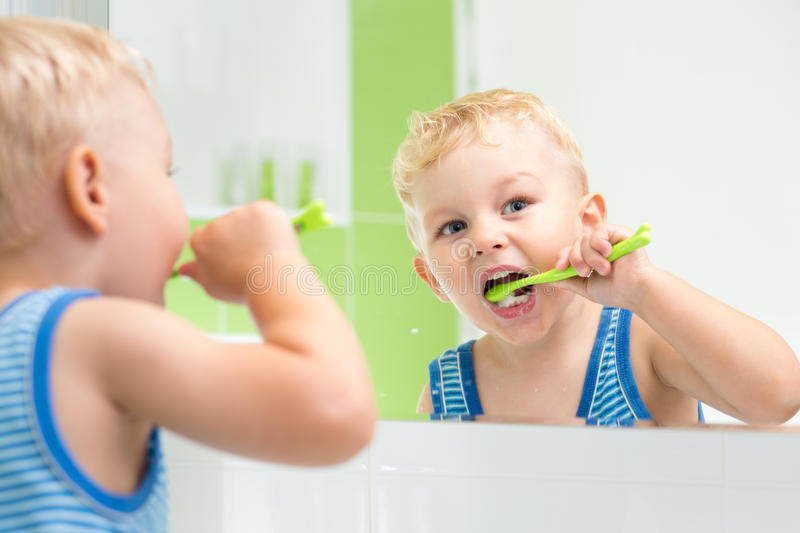 Kid boy brushing teeth royalty free stock photography
