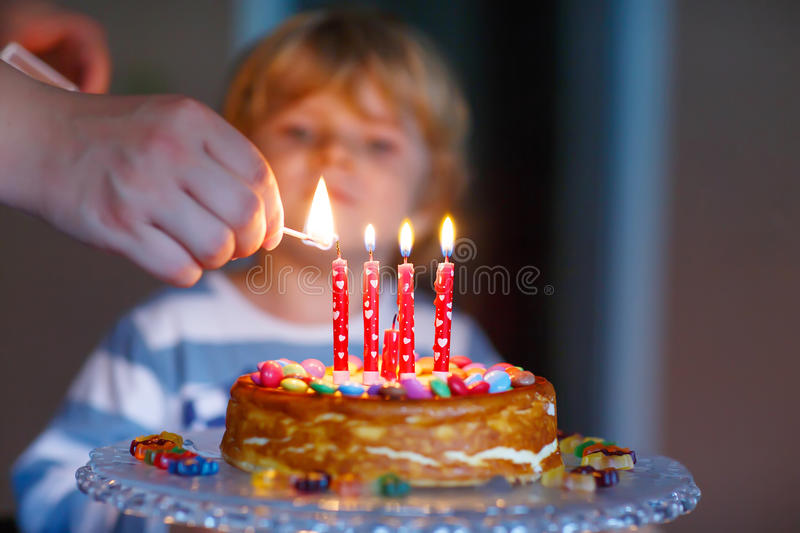 Kid boy celebrating his birthday and blowing candles on cake royalty free stock photography