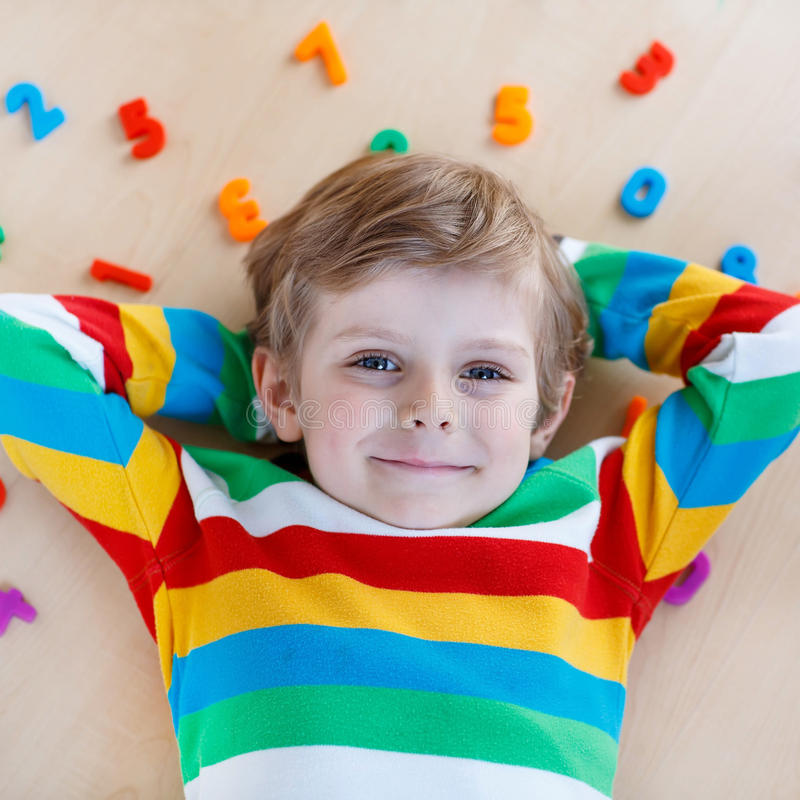 Kid boy with colorful numbers, indoor. Little blond child playing with lots of colorful plastic digits or numbers, indoor. Kid boy wearing colorful shirt and royalty free stock image