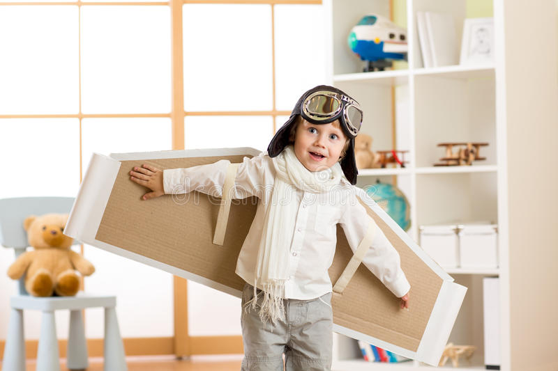 Kid boy dressed as pilot or aviator plays with handmade paper wings in his room royalty free stock images