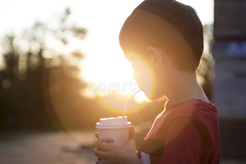 Kid boy drinks cocoa or soda in a cup with tube on sunset background. Silhouette of a drinking boy at sunset.  royalty free stock image