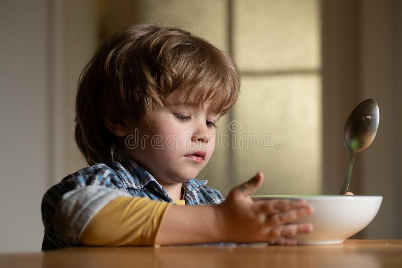 Kid boy eating healthy food at home. Good morning in Happy family. Little boy sitting at the table and eating milk snack stock image