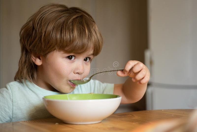 Kid boy eating healthy food at home. Happy child have a breakfast. Portrait of beautiful child having breakfast at home. Smiling happy adorable baby eating royalty free stock images