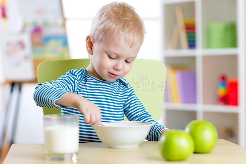 Kid boy eating healthy food at home or kindergarten. Kid eating healthy food at home or kindergarten stock photography