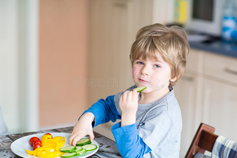 Kid boy eating healthy food in kindergarten or at home. Happy adorable kid boy eating healthy food in kindergarten or at home. Fresh vegetables as snack for stock photos
