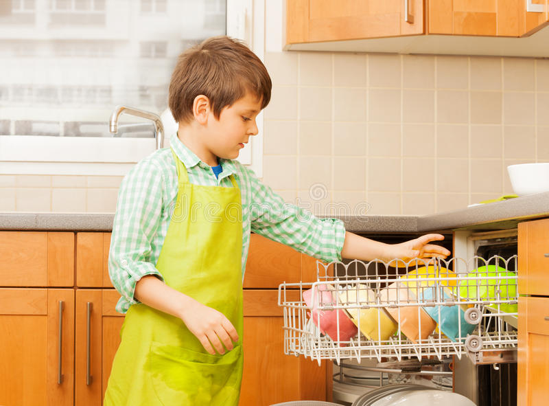 Kid boy getting out clean crockery of dishwasher stock photo
