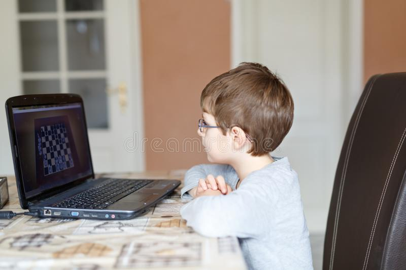 Kid boy with glasses playing online chess board game on computer. Little school kid boy with glasses playing online chess board game on computer. Child having royalty free stock photo