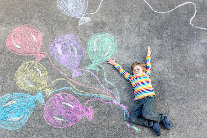 Kid boy having fun with colorful balloons drawing with chalks stock photography