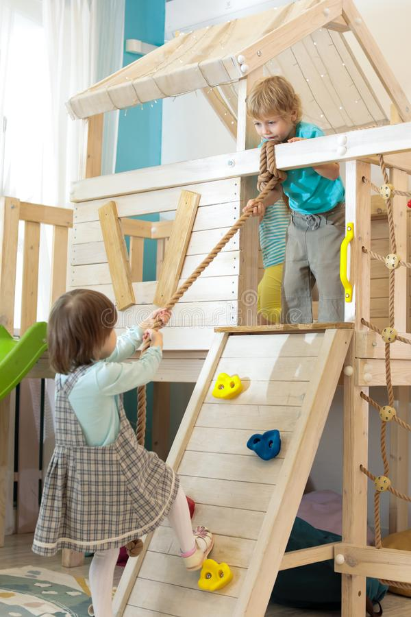 Kid boy helps child girl climb the rope up in playroom royalty free stock photo