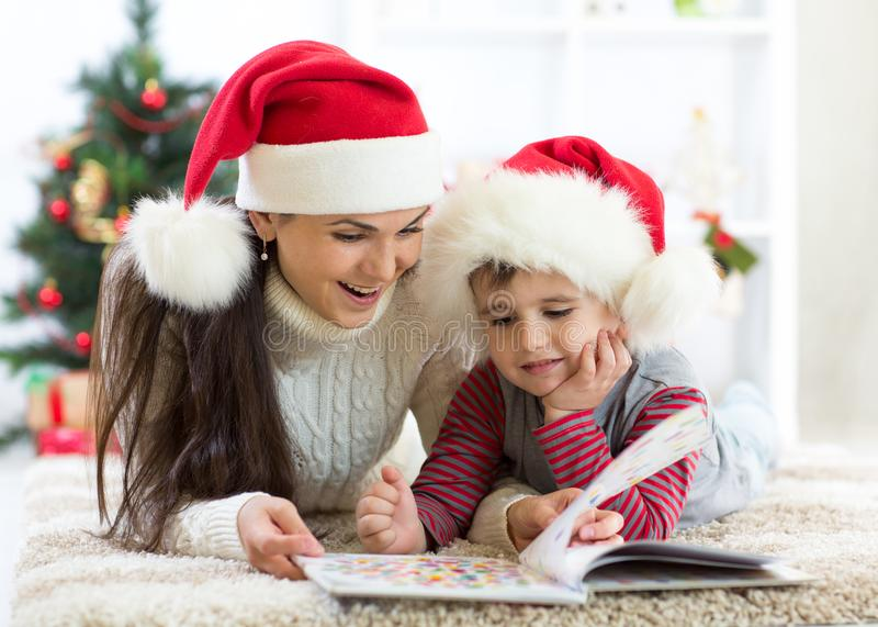 Kid boy and his mom reading book at Christmas royalty free stock photography