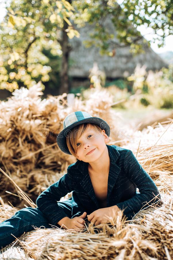 Kid boy lies on the hay. Boy in the hat are preparing for autumn sunny day. Little boy are getting ready for autumn sale royalty free stock image