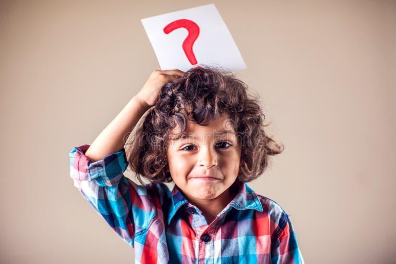 Kid boy med frågetecken Begreppet barn, utbildning och känslor royaltyfri fotografi