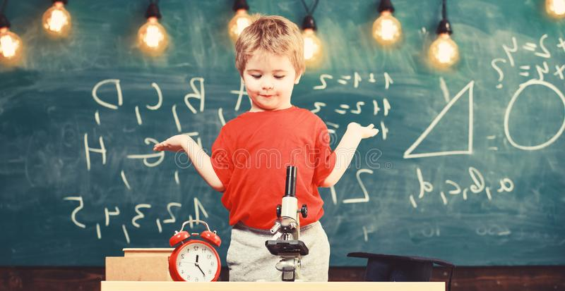 Kid boy near microscope, clock in classroom, chalkboard on background. First former confused with studying, learning royalty free stock photos