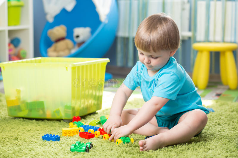 Kid boy playing with building blocks at home or kindergarten. Kid boy plays with building blocks at home or kindergarten stock image