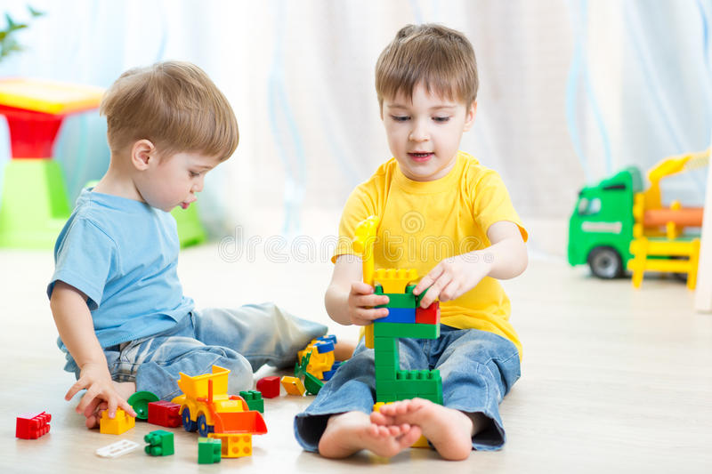 Kid boy playing with little brother at home stock images