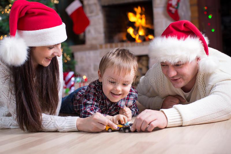 Kid boy playing toy cars with his parents under the christmas tree stock images