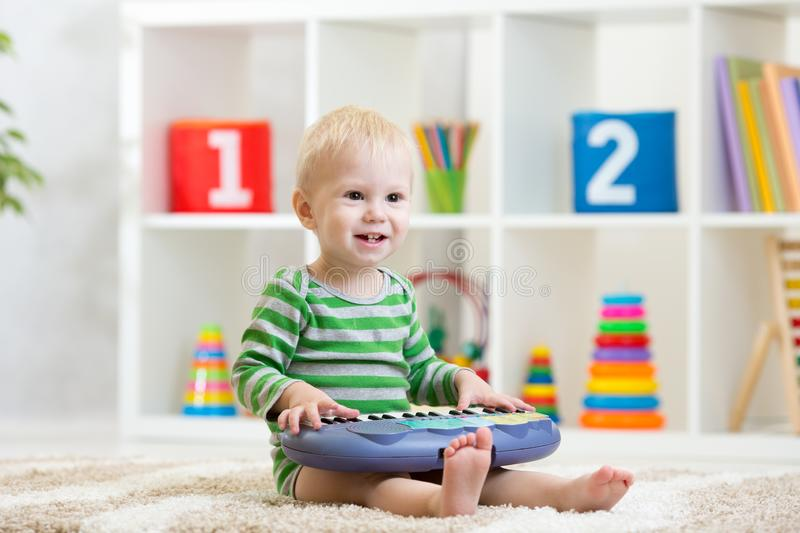 Kid boy playing toy piano in nursery royalty free stock photography