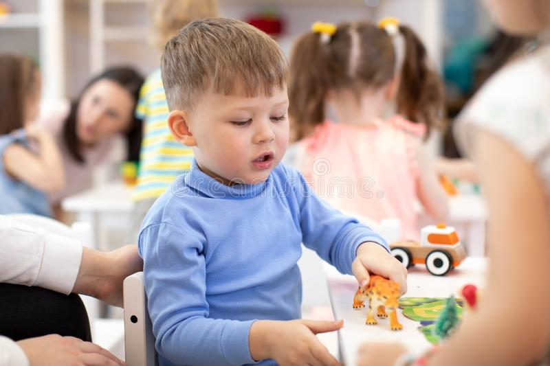 Kid boy plays animal toy in kindergarten. Group of preschool kids on lesson in class royalty free stock photo