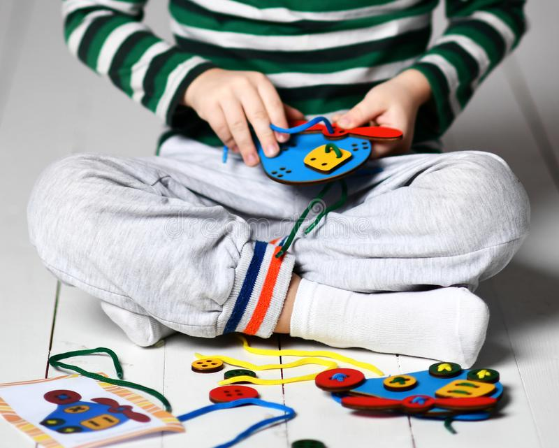 Kid boy plays educational game interestedly with wooden colorful helicopter and laces royalty free stock photo