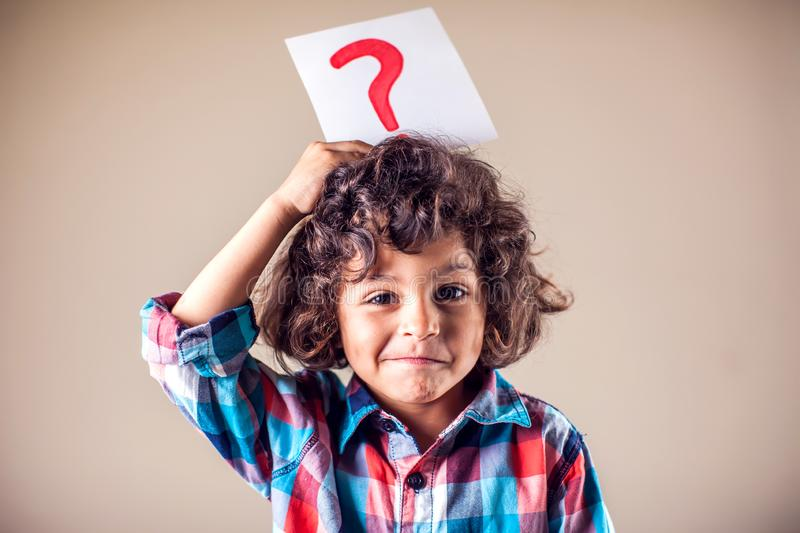 Kid boy with question mark. Children, education and emotions concept royalty free stock photography